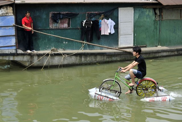 Lei Zhiqian rides a modified bicycle across the Hanjiang River, a tributary of the Yangtze River in Wuhan, Hubei province, China, June 16, 2010. The bicycle, equipped with eight empty water containers at the bottom, was modified by Lei's instructor Li Weiguo, who hopes to put his invention into the market. (Photo by Reuters/China Daily)