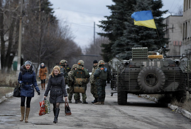 Women residents pass by a group of the Ukrainian government army soldiers in the village of Debaltseve, Donetsk region, eastern Ukraine Wednesday, December 24, 2014. (Photo by Sergei Chuzavkov/AP Photo)