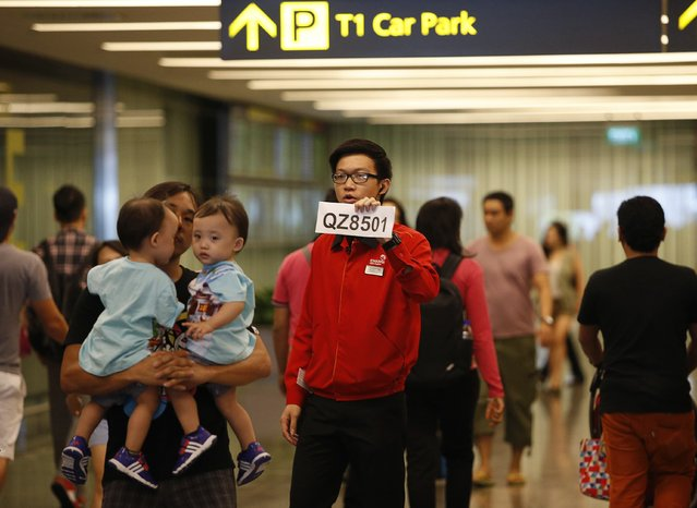 A Changi Airport staff holds up a sign to direct possible next-of-kins of passengers of AirAsia flight QZ 8501 from Indonesian city of Surabaya to Singapore, at Changi Airport in Singapore December 28, 2014. (Photo by Edgar Su/Reuters)