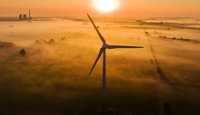 The morning mist is illuminated by the rising sun over fields and wind turbines near Sehnde, Germany, 19 August 2016. The Mehrum coal-fired power station is visible on the horizon. (Photo by Julian Stratenschulte/EPA)
