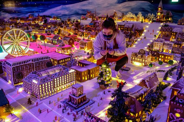 An employee squats between exhibits of the traditional Gingerbread Town in Bergen, Norway, as it opened on December 8, 2020. Miniature houses, trains, cars and ships are made from real gingerbread. Schools and kindergardens contribute every year in making a miniature version of Bergen – all in gingerbread-cookies. (Photo by Marit Hommedal/NTB via AFP Photo)