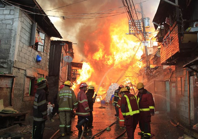 Firefighters douse water as they try to put out a raging fire that engulfed around 2,000 houses in Quezon city, metro Manila January 1, 2015. (Photo by Romeo Ranoco/Reuters)