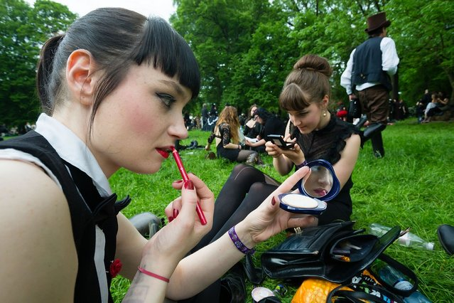 Two girls in black clothing refresh their make-up during the traditional park picnic on the first day of the annual Wave-Gotik Treffen, or Wave and Goth Festival, on May 17, 2013 in Leipzig, Germany. The four-day festival, in which elaborate fashion is a must, brings together over 20,000 Wave, Goth and steam punk enthusiasts from all over the world for concerts, readings, films, a Middle Ages market and workshops. (Photo by Marco Prosch)