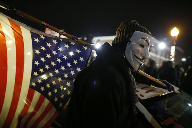 Ferguson, Missouri: A protester wearing a Guy Fawkes mask carries an American flag outside the Ferguson Police Department in Ferguson, Missouri, November 24, 2014. Missouri Governor Jay Nixon urged people in the St. Louis area to show respect and restraint following a grand jury's decision on whether to criminally charge a white police officer in the August fatal shooting of unarmed black teenager Michael Brown. (Photo by Jim Young/Reuters)