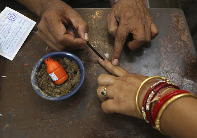 A polling officer marks the finger of a woman voter with indelible ink at a polling station in Bangalore, India, Saturday, May 12, 2018. India's southern state of Karnataka headed to the polls Saturday to elect 224 lawmakers ahead of country's general elections in 2019. (Photo by Aijaz Rahi/AP Photo)