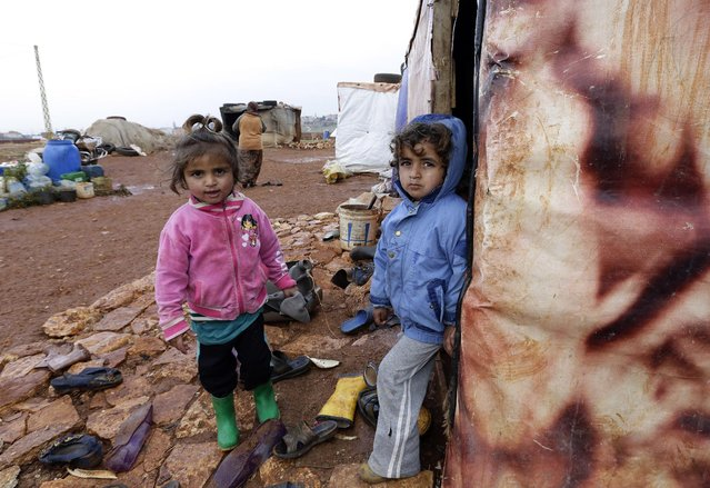 Umm Ali's children who fled the violence in the northern Syrian city of Aleppo, play at the entrance of their tent at an unofficial refugee camp in Jabaa, a village in the Bekaa Valley in Lebanon on December 20, 2014. With just blankets to shield them against the icy wind and rain tens of thousands of Syrian refugees in Lebanon are inadequately equipped to cope as winter sets in. (Photo by Anwar Amro/AFP Photo)