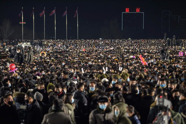 Attendees gather to watch a performance during New Year celebrations at Kim Il Sung square in Pyongyang on January 1, 2021. (Photo by Kim Won Jin/AFP Photo)