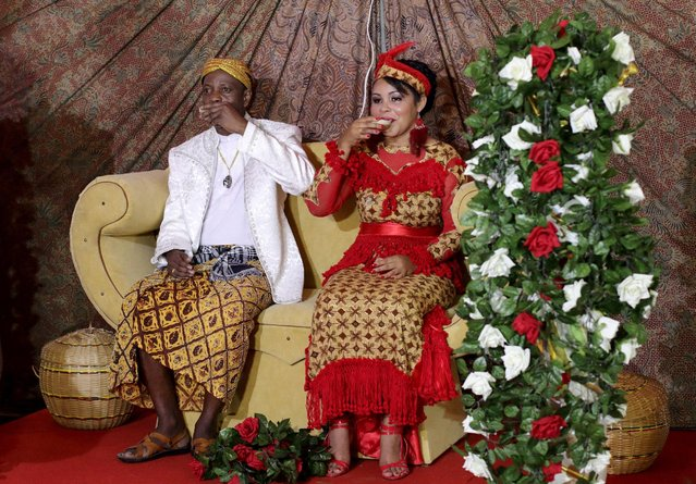 Winti spiritual leader Ramon Mac-Nack (L) and his bride Melissa Karwafodi toast after being wedded in the first Winti marriage ever to be held in public, in district Para, Suriname, November 16, 2015. The Winti religion, which formed centuries ago out of elements of different religious traditions that African slaves brought with them to Suriname, was considered a form idolatry and prohibited by law since the days of slavery until it was finally officially recognized in 1971. (Photo by Ranu Abhelakh/Reuters)