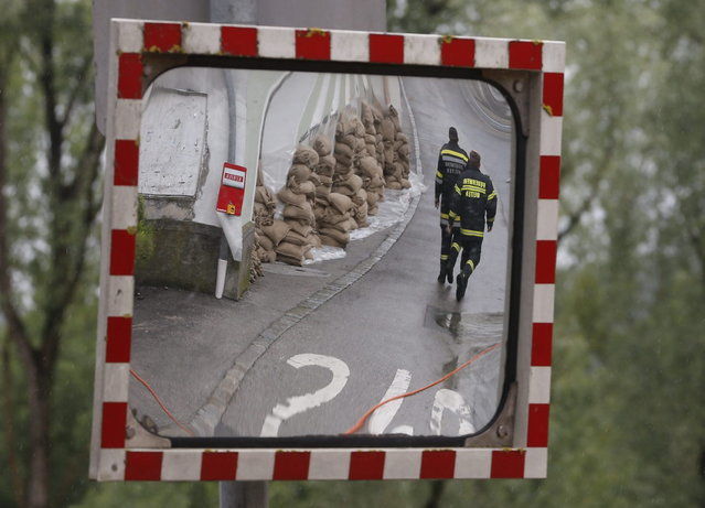 Members of the emergency services walking past sand bags protecting a building from flood water, are reflected in a traffic mirror in a street in the centre of the Austrian town of Melk, about 100 km (62 miles) west of Vienna June 3, 2013. Torrential rain in Tyrol, Salzburg, Upper and Lower Austria caused heavy flooding over the weekend, forcing people to evacuate their homes. (Photo by Leonhard Foeger/Reuters)