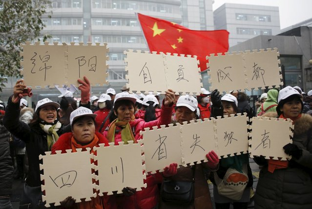 Parents who lost their only child hold signs as they gather in front of the National Health and Family Planning Commission office in Beijing, China, December 1, 2015. Hundreds of such parents demanded financial and legal support from the government for the loss of their only child, according to participants of the gathering. (Photo by Kim Kyung-Hoon/Reuters)