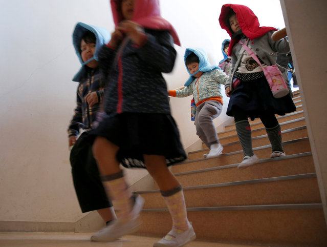 School children wearing padded hoods to protect them from falling debris take part in a tsunami simulation drill ahead of World Tsunami Awareness Day at Futaba elementary school in Choshi, Chiba Prefecture, Japan, November 4, 2016. (Photo by Kim Kyung-Hoon/Reuters)