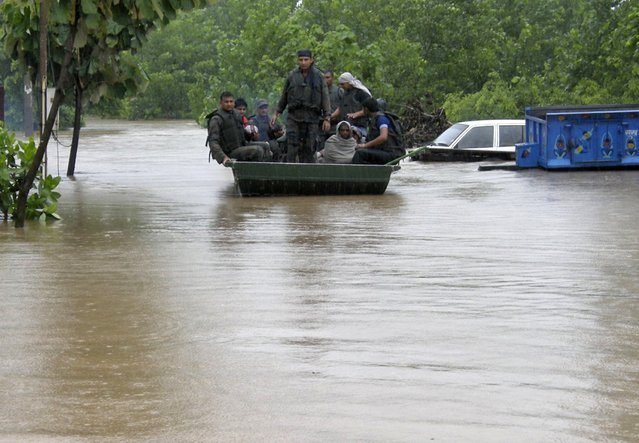Indian army soldiers rescue stranded villagers in a boat after floods triggered by heavy rains at Odhri village in Yamunanagar district of the northern Indian state of Haryana June 17, 2013. The rains usually cover all of India by mid-July, but this year it happened on June 16, the earliest such occurrence on record, a senior official at the India Meteorological Department said. (Photo by Reuters/Stringer)