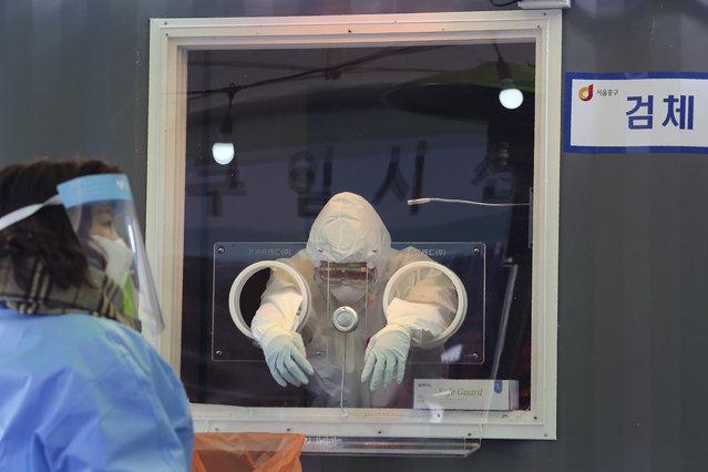 A medical worker in a booth rests during COVID-19 testing at a makeshift clinic in Seoul, South Korea, Saturday, January. 2, 2021. South Korea is extending stringent distancing rules for two more weeks as authorities seek to suppress a viral resurgence, while confirming its first case of an apparently more contagious coronavirus variant detected in South Africa. (Photo by Ahn Young-joon/AP Photo)