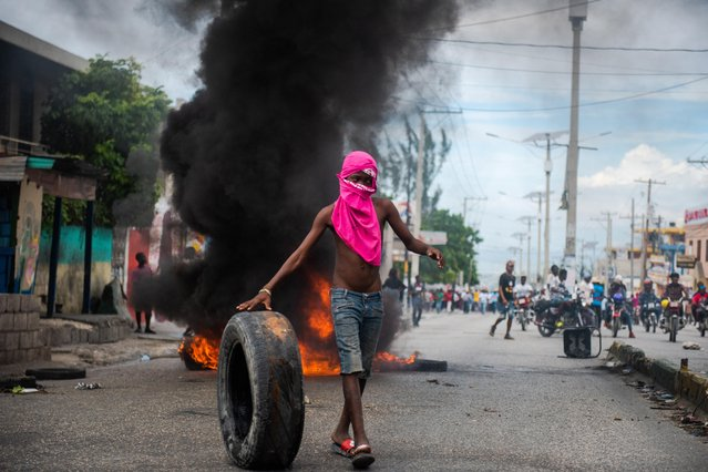 A person demonstrates to demand the resignation of President Moise, who is accused by the opposition of corruption, in the streets of Port-au-Prince, Haiti, 18 November 2020. At least one person has been killed and several injured during two demonstrations against the country's president Jovenel Moise and drafting of a new Constitution, on 19 November 2020. (Photo by Jean Marc Herve Abelard/EPA/EFE)