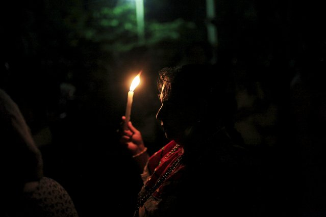 A devotee carries a lit candle to celebrate the Day of the Virgin of Guadalupe outside the Basilica of Guadalupe in San Salvador, El Salvador December 12, 2015. (Photo by Jose Cabezas/Reuters)