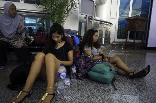 Passengers wait at Ngurah Rai international airport, Indonesia on Thursday, June 28, 2018, as airlines canceled flights. The Mount Agung volcano has shot ash 2,000 meters into the atmosphere, disrupting the travel plans of thousands as several airlines canceled flights from the Indonesian tourist island. (Photo by Firdia Lisnawati/AP Photo)