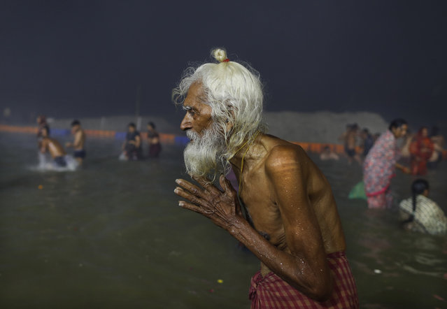 An elderly pilgrim prays after a holy dip at the Sangam in Prayagraj, India, Thursday, February 11, 2021. When the coronavirus pandemic took hold in India, there were fears it would sink the fragile health system of the world's second-most populous country. Infections climbed dramatically for months and at one point India looked like it might overtake the United States as the country with the highest case toll. But infections began to plummet in September, and experts aren't sure why. (Photo by Rajesh Kumar Singh/AP Photo)