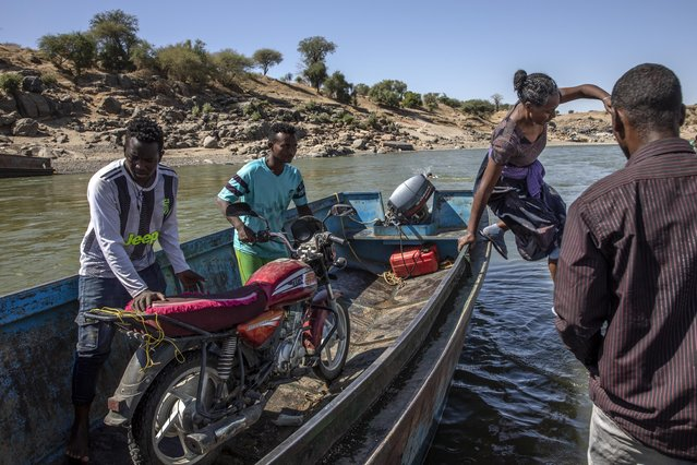 Tigray refugees who fled the conflict in the Ethiopia's Tigray arrive with their motorcycle on the banks of the Tekeze River on the Sudan-Ethiopia border, in Hamdayet, eastern Sudan, Tuesday, December 1, 2020. (Photo by Nariman El-Mofty/AP Photo)