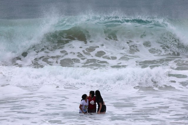 Catholic pilgrims embrace while standing in the sea as they await the arrival of Pope Francis on Copacaban beach in Rio de Janeiro, on July 25, 2013. (Photo by Ricardo Moraes/Reuters)