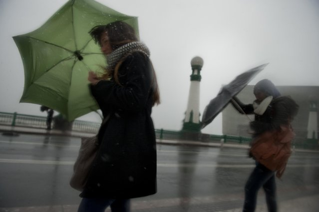 Women struggle to walk across a bridge as the wind blows, in San Sebastian, northern Spain, Friday, January 30, 2015. Authorities have announced gale-force winds in upcoming days of up to 100 kilometers per hour (62 miles per hour). (Photo by Alvaro Barrientos/AP Photo)