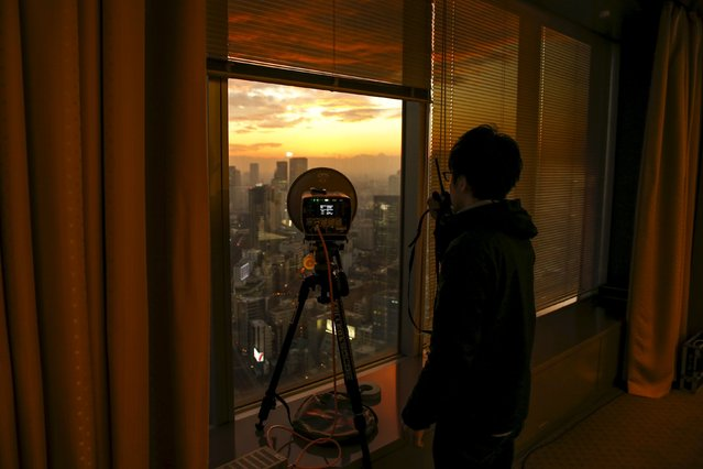 A TV technician talks with his newsroom about the signal strength a device is transmitting from the news conference room on 39th floor of the Toshiba head office as the sun sets over Tokyo, Japan, December 21, 2015. Japan's Toshiba Corp said on Monday it will cut nearly 7,000 consumer electronics jobs after a $1.3 billion accounting scandal, in an overhaul that will streamline the sprawling conglomerate into a company focused on chips and nuclear energy. (Photo by Thomas Peter/Reuters)