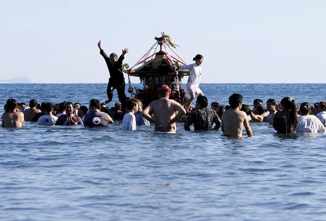 "A woman jumps from a ""mikoshi"" or portable shrine as people carry it into the sea during a festival to wish for calm waters in the ocean and good fortune in the new year in Oiso, Kanagawa prefecture, west of Tokyo, Japan, January 1, 2016. (Photo by Yuya Shino/Reuters)"