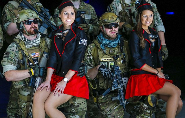 Men dressed as soldiers pose with models before the opening of the Gamescom 2013 fair in Cologne,Germany, on August 23, 2013. The Gamescom convention is Europe's largest video games trade fair. (Photo by Ina Fassbender/Reuters)