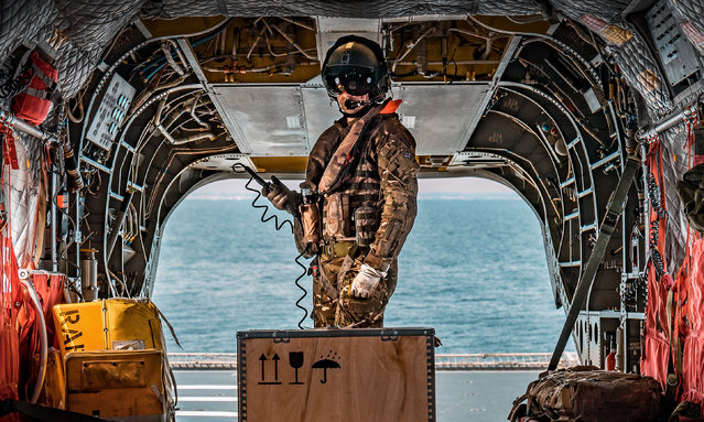 """""""This Way Up"""". Photographic section portfolio, first prize. A Chinook CH-47 weapon systems operator prepares his aircraft during a training exercise in June 2018. (Photo bu SAC Ed Wright/RAF)"""