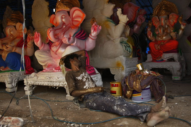 An Indian artist takes a rest as he prepares idols of elephant-headed Hindu god Ganesh ahead of Ganesh Chaturthi festival at a workshop in Hyderabad, India, Monday, September 2, 2013. Ganesh Chaturthi, which begins from September 9, is celebrated as the birthday of Lord Ganesha who is widely worshiped by Hindus as the god of wisdom, prosperity and good fortune. (Photo by Mahesh Kumar A./AP Photo)
