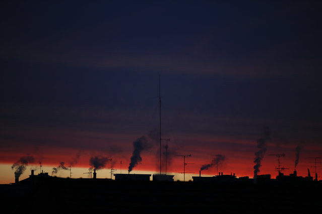 Plumes of smoke billow from some silhouetted chimneys part of the Milan skyline at dawn, Italy,Thursday, January 7, 2016. (Photo by Luca Bruno/AP Photo)