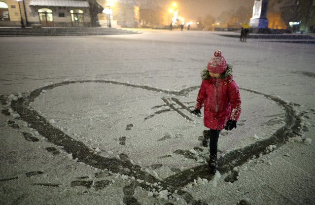 A young girl plays in the snow in the Castle Square in Warsaw, Poland, 25 December 2014. According to the weather forecast temperatures in the Polish capital will drop during the next days to be between minus three and minus five degrees Celsius. (Photo by Jacek Turczyk/EPA)