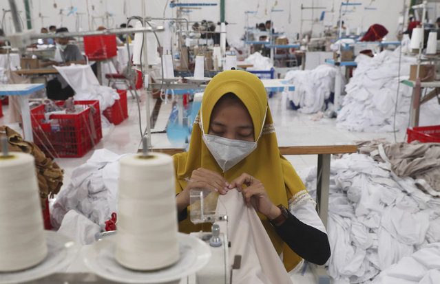 Workers wearing face masks to curb the spread of the coronavirus outbreak operate sewing machines at a factory that makes Muslim women's prayer robes in Depok, Indonesia, Wednesday, April 7, 2021. (Photo by Tatan Syuflana/AP Photo)