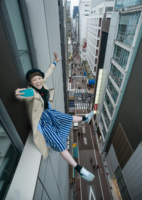 A woman perches on a window ledge in Tokyo to take a selfie. (Photo by Petri Artturi Asikainen/Getty Images )