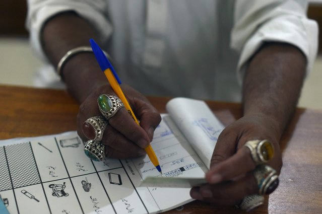 A election official man notes down information of an ID of a voter during Pakistan's general election at a polling station in Lahore on July 25, 2018. Pakistanis voted July 25 in elections that could propel former World Cup cricketer Imran Khan to power, as security fears intensified with a voting-day blast that killed at least 28 after a campaign marred by claims of military interference. (Photo by Wakil Kohsar/AFP Photo)