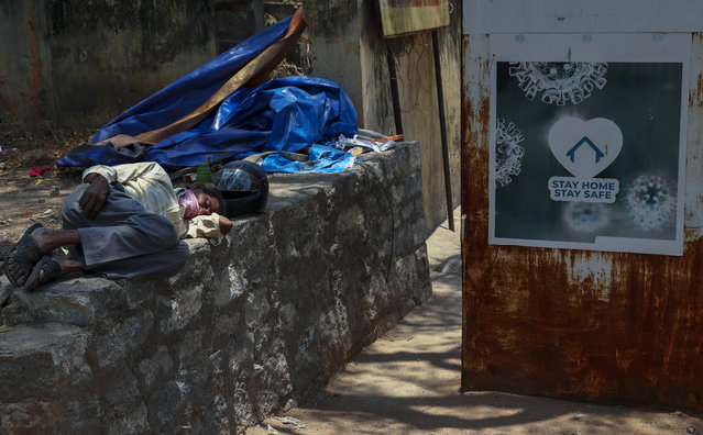 An Indian man sleeps next to a signage urging people to stay at home as a precaution against coronavirus in the premises of a hospital in Hyderabad, India, Thursday, April 29, 2021. (Photo by Mahesh Kumar A./AP Photo)