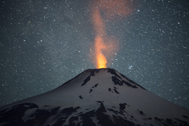 A long exposure picture taken on 14 February 2015 showing Villarrica volcano, in the La Araucania region, 700 km south of Santiago, Chile. Geological and emergency services maintained the early preventive state warning in four municipalities near the volcano whose activity has increased in recent days. (Photo by Francisco Negroni/EPA)