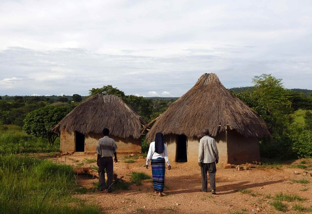 HIV-positive 71-year-old Sylverio Hachiploa (right) walks with caregivers Glandwel Muleya (L) and Sister Abigail Mwaka Mazuba (C) during a visit by a home-based care team in the village of Nedwmba, south of the Chikuni Mission in the south of Zambia February 23, 2015. (Photo by Darrin Zammit Lupi/Reuters)