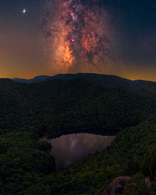 """ADK magic; Adirondack Mountains, New York, US. """"The east coast is less commonly known for Milky Way photography due to its condensed population and, as a result, intense light pollution. However, there are still a few dark skies remaining … tucked away in upstate NY, the Adirondacks region consists of 6m acres of land designated as """"forever wild"""". It is home to some of the last known darkest skies on the east coast. I feel like I am home when I am hiking in the Adirondacks. This shot, then, captures the magic which I feel fills my heart when I am there. Not only does it consist of a lake which seems to take the formation of a heart itself, but it also shows just how much the east coast has to offer: beautiful woodlands combined with still water and rolling hills. My heart is in these mountains, and I am so thankful to be able to explore them. With that in mind, these mountains are constantly being swarmed with light pollution. The yellow glow on the horizon is light pollution from within the region as well as way off in the distance. My goal is to attempt to use my photography to raise awareness about the issue and restore the night. Remember: if you plan to visit the region, please read up on all current regulations, and leave no trace on site"""". (Photo by Daniel Stein/Milky Way Photographer of the Year)"""