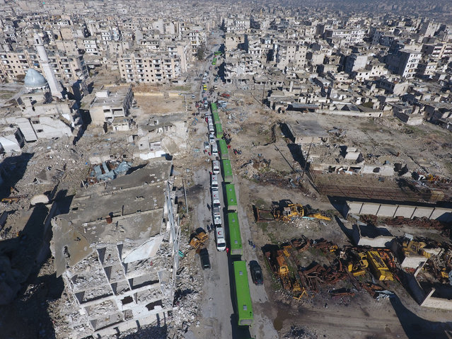 An aerial view show a convoy including busses and ambulances, wait at a crossing point at Amiriyah District of Aleppo, Syria on December 15, 2016 to evacuate civilians, trying to flee from East Aleppo where had been under siege by Iran led Shiite militias and Assad Regime forces. (Photo by Hasan Katan/Anadolu Agency/Getty Images)