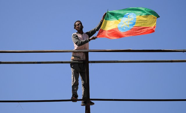 A pro-government demonstrator holds their national flag as people attend a rally to protest against the U.S. action over alleged human rights abuses during the conflict in the Tigray region, in Addis Ababa, Ethiopia on May 30, 2021. (Photo by Tiksa Negeri/Reuters)