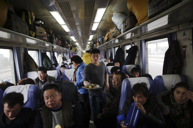 A man carries food on a train travelling from Shanghai to Shijiazhuang after migration for the annual Chinese Lunar New Year and Spring Festival began. Picture taken January 27, 2016. (Photo by Aly Song/Reuters)