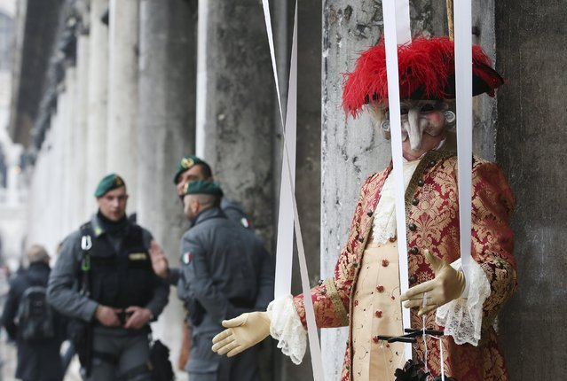 A masked reveller (R) poses in San Marco Piazza next to Italian Finance Police personnel during the Venice Carnival, January 30, 2016. (Photo by Alessandro Bianchi/Reuters)