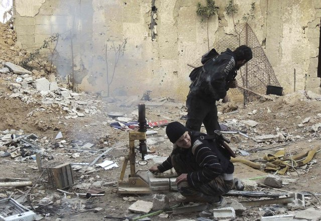 Rebel fighters from the Free Syrian Army's Al Rahman legion fire a mortar at the frontline against forces loyal to Syria's President Bashar al-Assad in Jobar, a suburb of Damascus January 28, 2015. (Photo by Yousef Homs/Reuters)