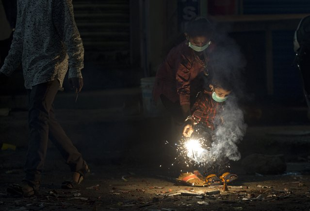 Indians light fire crackers wearing masks to fight pollution as they celebrate Diwali, the festival of lights in Hyderabad, India, Wednesday, November 7, 2018. India's top court recently ruled that only less polluting firecrackers should be manufactured and sold. (Photo by Mahesh Kumar A./AP Photo)