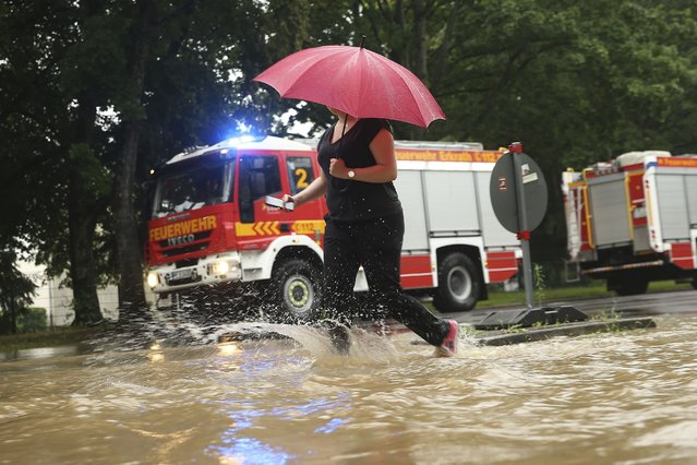 A woman walks past fire trucks at a flooded street with an umbrella Duesseldorf, Germany, Wednesday, July 14, 2021. Storms caused widespread flooding across central Germany overnight, with authorities warning that more rain is on the way. (Photo by David Young/dpa via AP Photo)