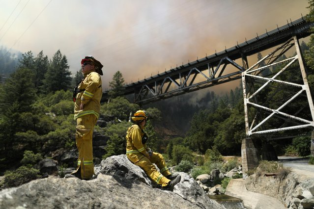 A Napa California crew monitors the Dixie Fire as it grows in Plumas National Forest, California, U.S., July 15, 2021. (Photo by David Swanson/Reuters)