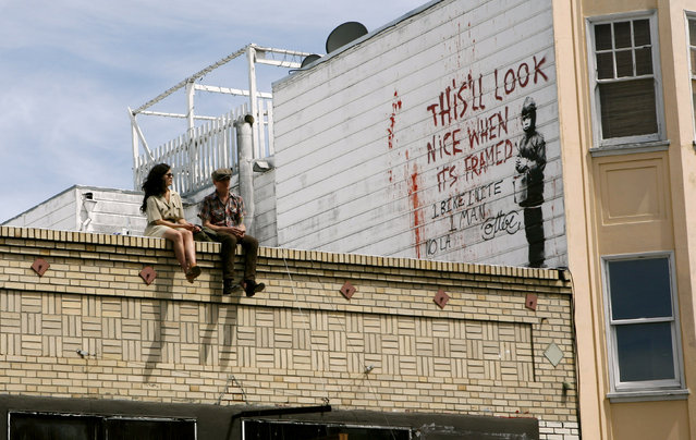 A couple sits on a rooftop featuring a painting, believed to be the work of elusive British street artist Banksy, in the Mission District of San Francisco, May 4, 2010. (Photo by Robert Galbraith/Reuters)