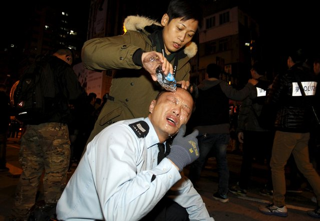 An injured policeman receives treatment after clashes with protesters at Hong Kong's Mongkok shopping district, China early February 9, 2016. (Photo by Liau Chung-ren/Reuters)