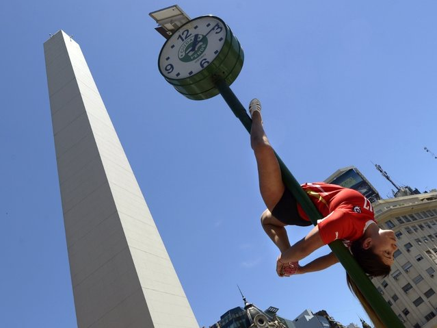 A Chilean participant in the Miss Pole Dance South America 2013 competition performs in in front of the obelisk in Republica Square in downtown Buenos Aires on November 22, 2013 ahead of the contest to be held on November 23 and 25 in the city. (Photo by Juan Mabromata/AFP Photo)