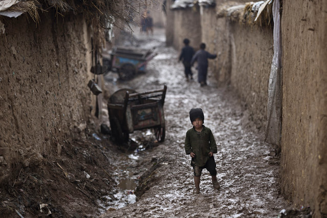 An Afghan refugee boy walks back to his family's mud home on sthe lippery ground of a slum during rainfall on the outskirts of Islamabad, Pakistan, Friday, February 20, 2015. (Photo by Muhammed Muheisen/AP Photo)